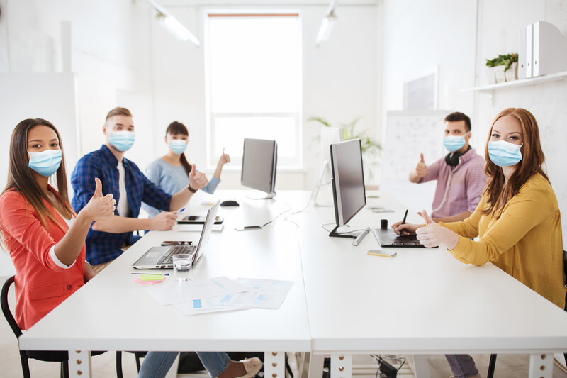 Five business people sitting in an office meeting wearing medical masks