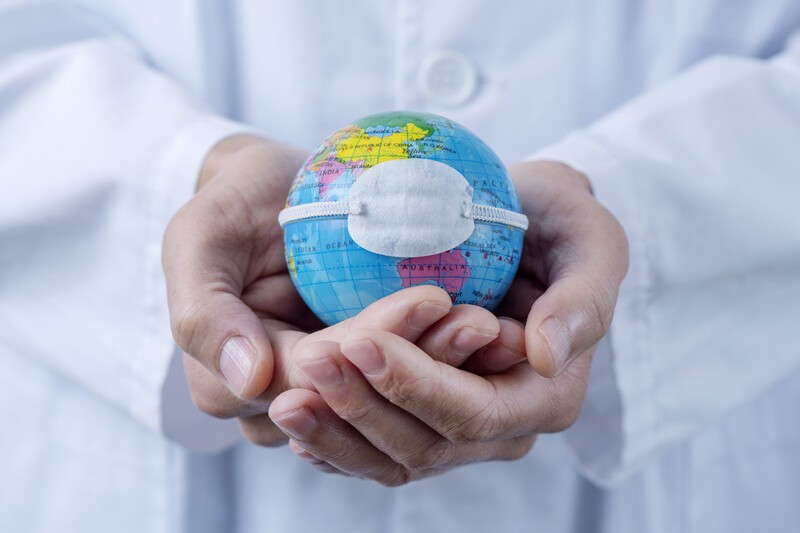Doctor holding small globe wearing a medical mask